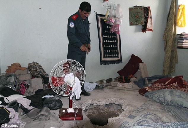 500名のタリバン受刑者が脱獄した穴を指す悲しげな刑務所所長 from Kandahar jail.jpg